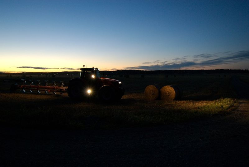 Tractor on a field in Sweden late summer evening