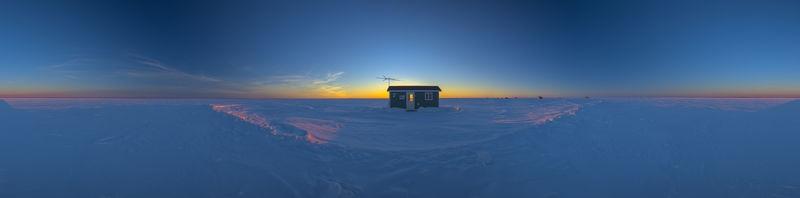 ice fishing house at sunset