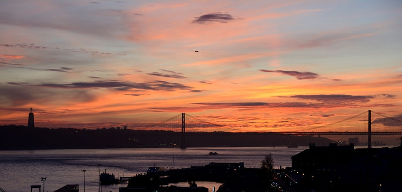 Sunset over the 25 de Abril Bridge and statue of Christ the King