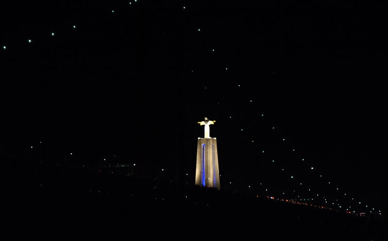Statue of Christ the King with the lights of the 25 de Abril Bridge